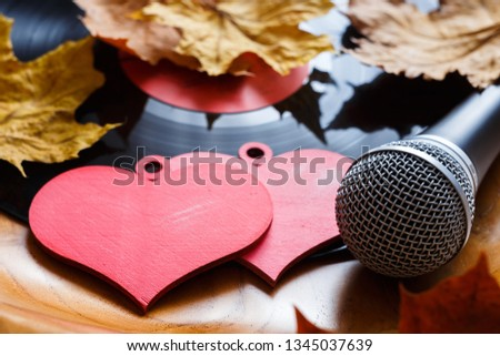 Song for lovers. Nostalgic songs, fallen autumn leaves and melancholy. Concept with vinyl records, microphone and hearts. #1345037639