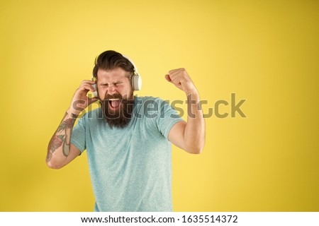 Song has healing power. Emotional song singer. Hipster sing song playing in headphones. Bearded man do vocal on song yellow background. Music makes me stronger, copy space.