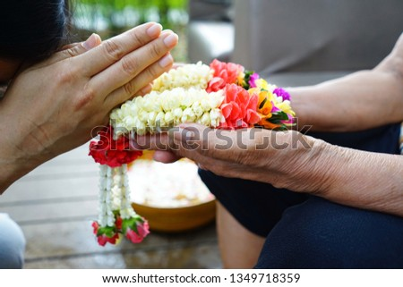 Songkran Festival and Thai New Year theme woman putting the hands together in sign of pay respects after giving Thai traditional jasmine garland to parents or revered elders, elderly people in family.