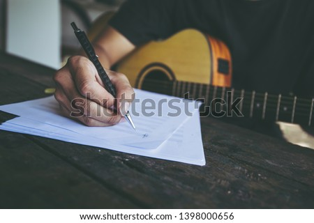 songwriter artist thinking writing notes,lyrics in book at studio.man playing live acoustic guitar.concept for musician creative.artist composer in work process.people relaxing time with instrument Stock photo ©