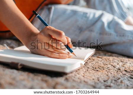 songwriter create and writing notes,lyrics in the book on stone at parks. Stock photo ©
