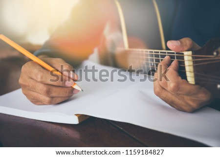 songwriter thinking and writing notes,lyrics in book at studio.man playing live acoustic guitar.concept for musician creative.artist composer in work process.people relaxing time with instrument Stock photo ©