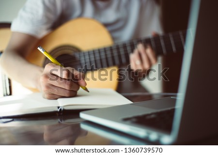 songwriter thinking and writing notes,lyrics in book at studio.man playing live acoustic guitar.concept for musician creative.artist composer in work process.people relaxing time with instrument Foto stock ©