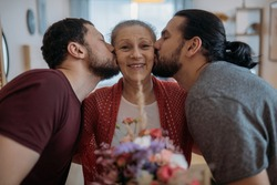 Sons congratulate mom on the holiday. Adult brothers give a bouquet of flowers to an elderly beautiful mother. Men visiting their beloved mother on a holiday