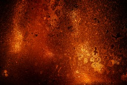 Soot stained fireplace glass door. the orange color of the burning fire on the spots glows.