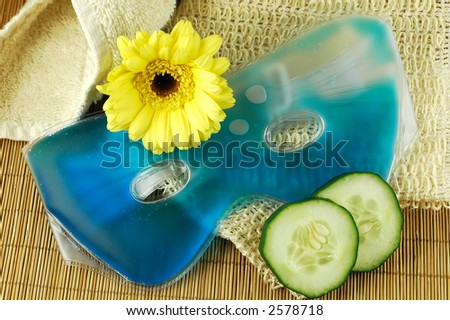 Soothing blue eye mask with cucumber slices, towel, natural fiber cloth, and yellow daisy on a bamboo mat