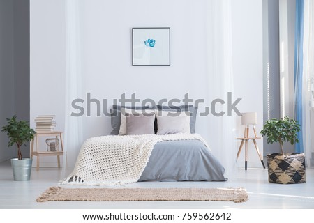 Soothing gray and blue color palette for balanced bedroom in cozy flat interior with plants and natural accessories