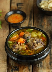 Sop buntut or Ox tail soup, served in black bowl on wooden table