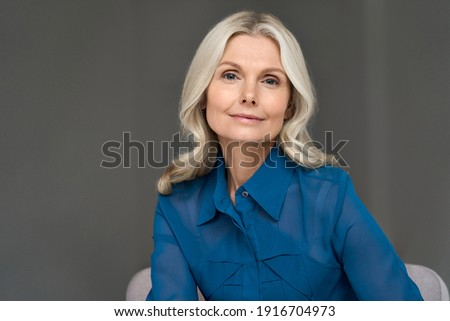 Sophisticated elegant beautiful 50s attractive middle aged smiling woman model sitting in chair looking at camera at home. Portrait of gorgeous confident mature older blond hair lady indoors.