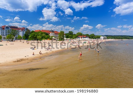 SOPOT, POLAND - 7 JUNE: People on the beach of Sopot at the Grand Hotel on 7 June 2014. Grand hotel built in 1924�1927 is the most refined hotel in Sopot - major health and tourist resort destination.