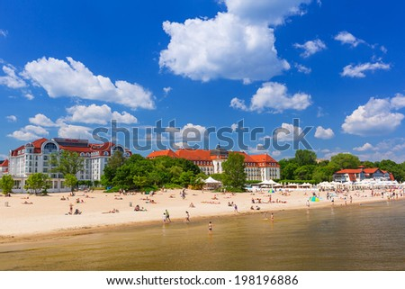 SOPOT, POLAND - 7 JUNE: People on the beach of Sopot at the Grand Hotel on 7 June 2014. Grand hotel built in 1924-1927 is the most refined hotel in Sopot - major health and tourist resort destination.