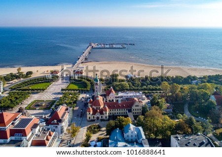 Sopot resort in Poland. SPA, old lighthouse, wooden pier (molo) with marina, yachts,  beach,  vacation infrastructure, park, promenade and walking people. Aerial view.