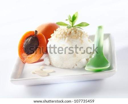 Sorbet icecream with almond topping and apricots served on a square white plate