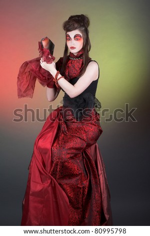 Sorceress. Lady in black and red dress and with fragment of mirror.