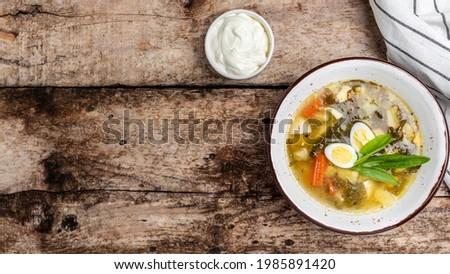 Sorrel soup with egg in bowl on the wooden table. Traditional Latvian soup. Skabenu zupa, banner, menu recipe place for text, top view. Zdjęcia stock ©