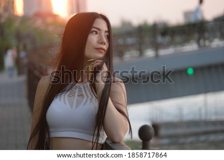 Sorrowful asian lady posing in sunset time on embankment looking away and leaning her chin on her hand, copyspace. Lovesick sweetheart in depression.