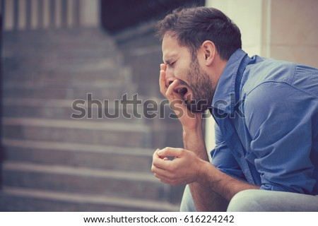 sorrowful crying young man sitting on steps outdoors