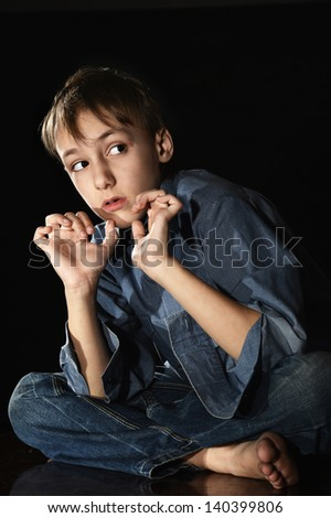 sorrowful little boy on a black background