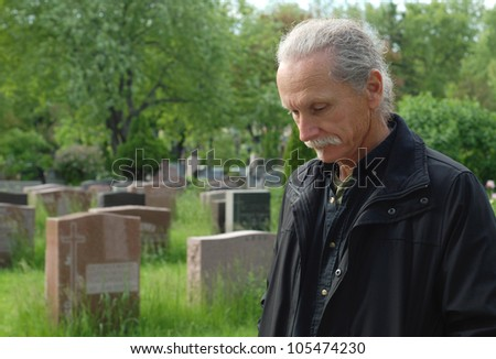 Sorrowful man standing in cemetery with head bowed