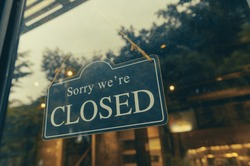 SORRY WE ARE CLOSED - Close sign broad hanging front of entrance door with copy space at coffee shop or restaurant