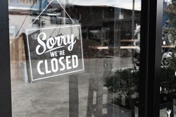 Sorry we're closed sign. grunge image hanging on a dirty glass door.