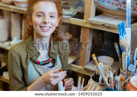 Sorting out paintbrushes. Beaming good-looking ginger girl holding professional paintbrush and inspecting state of her hairs #1409010623