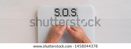 SOS written on weight scale screen woman weighting herself in on bathroom floor needing help to lose fat - obesity banner panoramic concept.