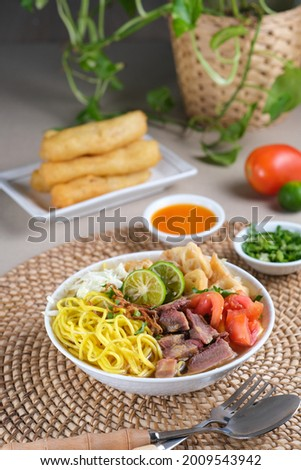 Soto Mie Bogor, Indonesian traditional beef noodle soup from West Java with noodles, beef, spring roll, cabbage, and tomato. Served with chili sauce and lime. Zdjęcia stock ©