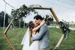 Soulful photo of the newlyweds hugging and kissing each other during the wedding ceremony