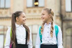 Soulmate friends. Cute schoolgirls with long ponytails looking charming. Ending of school year. Cheerful smart schoolgirls. Happy schoolgirls outdoors. Small schoolgirls wear school uniform.