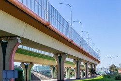Sound absorbing screens on the highway and overpass and colored concrete pillars. Metal frames filled with glass. Modern technology in Warsaw,Poland.