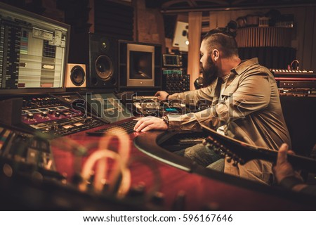 Sound engineer and guitarist recording song in boutique recording studio. #596167646