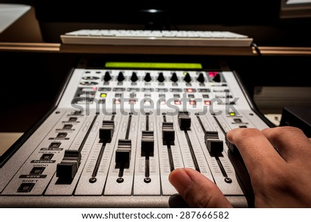 sound engineer hand on digital music studio mixer for recording or radio / tv broadcast background