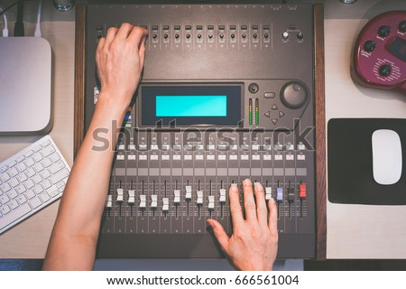 sound engineer hands working on digital sound mixer, music recording concept
