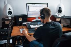 Sound engineer in headphones working and mixing music indoors in the studio.
