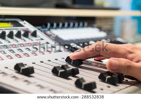 sound engineer right hand on digital studio mixer fader for music recording, radio / tv broadcasting  background