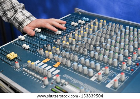 sound engineer\'s hand moving sliders on audio mixing board
