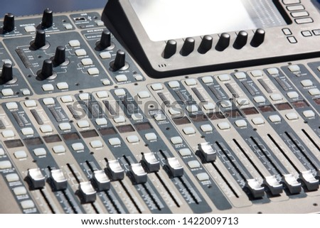 Sound mixer console detail with sliders and levels. Audio equipment