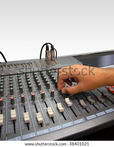 Sound Mixer Console of a Record Studio. Hand of a man making adjustments with a control knob. White background