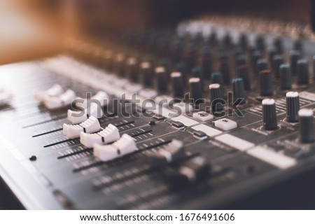 Sound mixer. Professional audio mixing console with lights, buttons, faders and sliders. Foto stock ©
