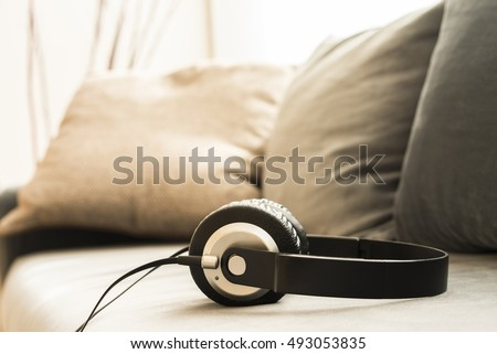 Sound music headphone (earphone) Stereo volume equipment object. Closeup photo of headphones on sofa with blurred background and copyspace area for a text. Audio technology, gadgets and music concept.