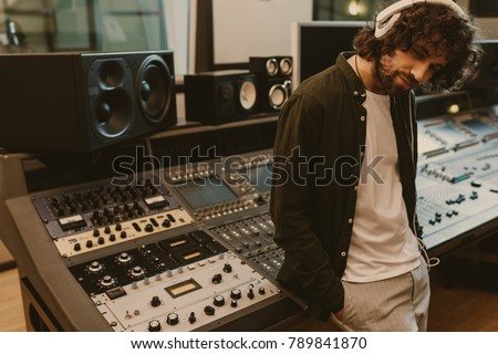 sound producer in headphones leaning back on recording equipment at studio #789841870