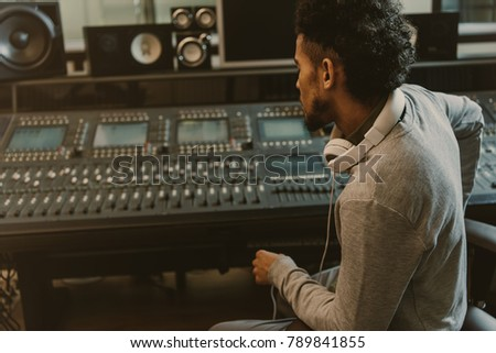 sound producer sitting in armchair and looking at graphic equalizer #789841855