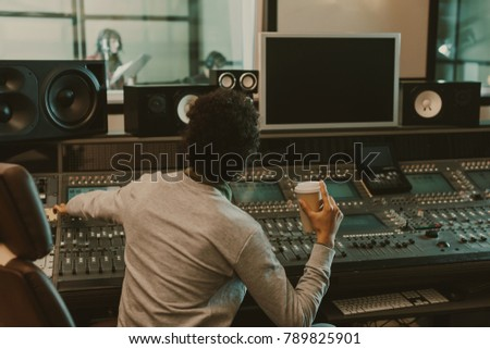 sound producer with disposable cup of coffee working at studio #789825901