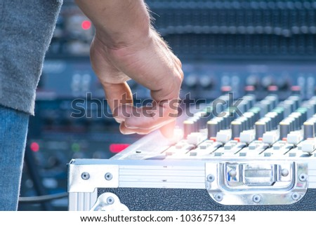 Sound technician and lights technicians control the music show in concert.Professional audio, light mixer controller panel.Pro equipment for concerts.Stage lighting control.Hand adjusting audio mixer #1036757134