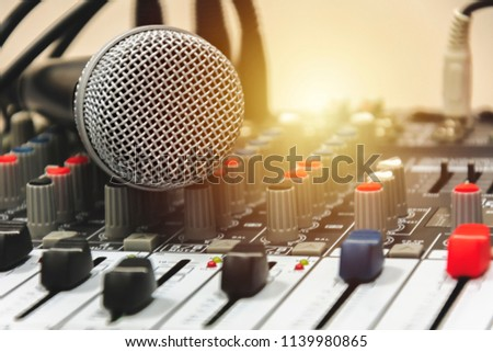 Sound technician control the music.Professional audio,Microphone put on mixer controller panel.Pro equipment for concerts. Stage lighting control.Hand adjusting audio mixer.  #1139980865