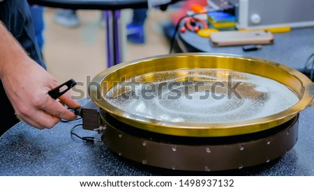 Sound vibration transforms white sand particles on steel surface at technology futuristic exhibition. Science, resonance and physics concept #1498937132
