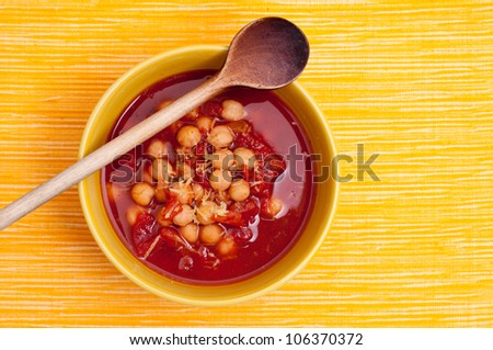 Soup peas and tomatoes in a yellow bowl with wooden spoon