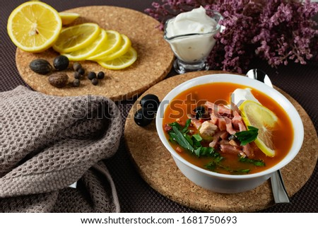 Soup Solyanka is a combined meat soup with smoked meat , various types of meat and tomato paste, serving dishes with sour cream, lemon and fresh herbs. Black olives on the table and a sprig of fresh f Stock fotó ©