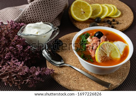 Soup Solyanka is a combined meat soup with smoked meat , various types of meat and tomato paste, serving dishes with sour cream, lemon and fresh herbs. Black olives on the table and a sprig of fresh  Stock fotó ©